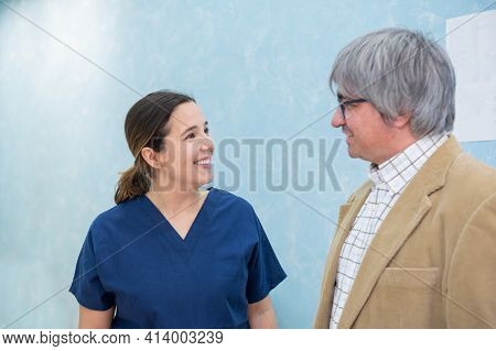 Young, Smiling Woman Doctor Chatting With Middle-aged Patient In Dental Clinic.health Care And Medic