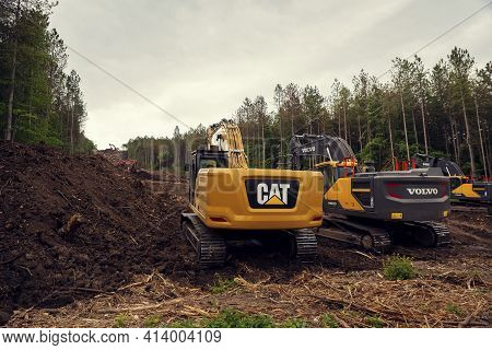 Bulgaria, Polski Trambesh, May 20th, 2020: Many Chain Excavators Digging The Terrain On A Slope Duri