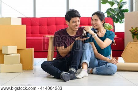 Happy Young Asian Married Couple Holding Key While Relocation Into New Home On Moving Day, Celebrati