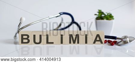 Bulimia The Word Is Written On Wooden Cubes And Sthetoscope And Piils . Medical Concept