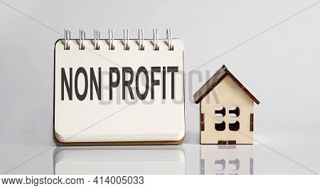 Non Profit Words Written In An Office Notebook With Wooden House. Business Concept.