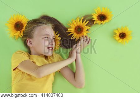 A Beautiful Girl With Sunflowers In Her Blonde Hair And A Yellow Baby Manicure On A Light Green Back