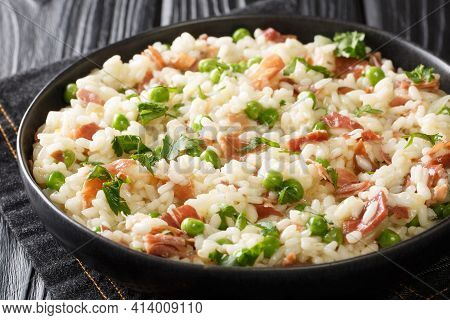 Italian Risotto Risi E Bisi Made From Rice With Peas And Ham Close-up In A Plate On The Table. Horiz