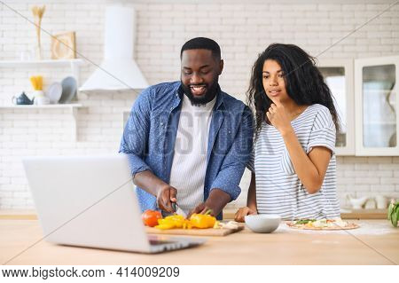 Happy African American Spouses Using Laptop Computer While Cooking In Modern Kitchen Together, Searc
