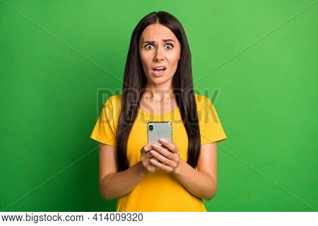 Photo Of Unhappy Scared Young Woman Hold Phone Dislike Reaction Addicted Blogger Isolated On Bright