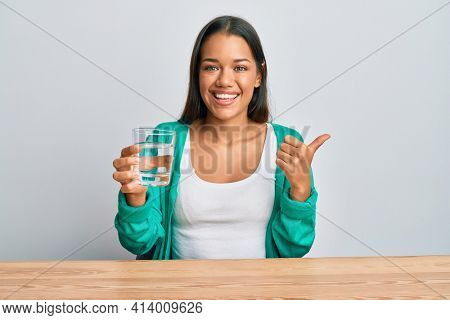 Beautiful hispanic woman drinking glass of water pointing thumb up to the side smiling happy with open mouth