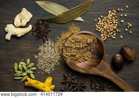 Assorted whole Indian spices spreaded over rustic wooden background. Aromatic and very flavorful Asian spice ingredients.