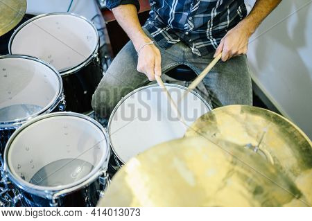 Close Up Of Man In Jeans And Plaid Shirt Playing Drums In Recording Studio.enjoying Music