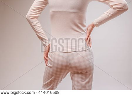 Beautiful Sexy Woman Wearing A Beige Pajama. Fashion Model On A Beige Background.