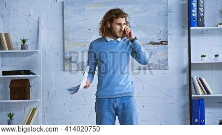 Discouraged Businessman Holding Papers While Talking On Smartphone In Office.