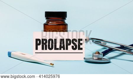 On A Blue Background - A Bottle For Pills, A Stethoscope, An Electronic Thermometer And A Card With
