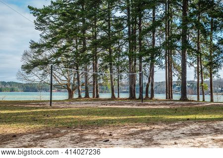 Volleyball Net Set Up On The Beach Area At The Lakefront At A Park With Trees And The Lake In The Ba