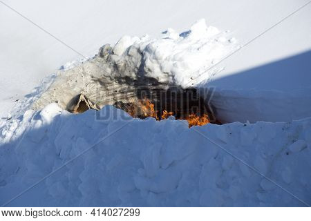 Burning Trash In The Snow. A Place For Incineration Of Household Waste In The Garden. Bonfire In A S