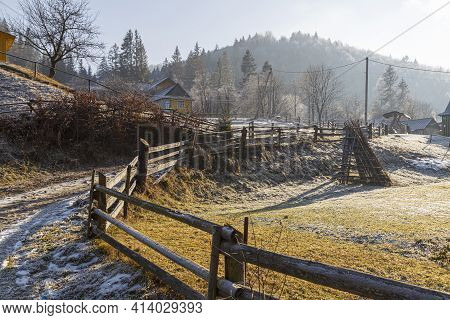 Sunny Frosty Foggy Day In A Mountain Village, Yaremche. Winding Road With A Wooden Fence. Carpathian