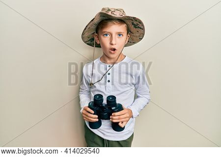 Little caucasian boy kid wearing explorer hat holding binoculars in shock face, looking skeptical and sarcastic, surprised with open mouth