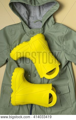 Baby Yellow Rubber Boots, Green Hooded Jacket On Beige Background. Waterproof Polymeric Footwear. Ra