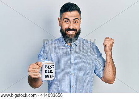 Young hispanic man drinking mug of coffee with best dad ever message screaming proud, celebrating victory and success very excited with raised arm