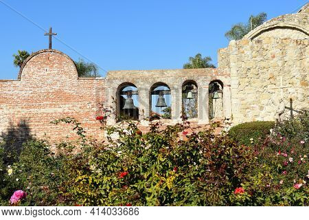 San Juan Capistrano, Ca - December 1, 2017: Mission Bell wall and Serra Statue with the Ruins of the Great Stone Church.