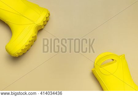 Baby Yellow Rubber Boots On Beige Background. Waterproof Polymeric Footwear. Children's Shoes. Flat