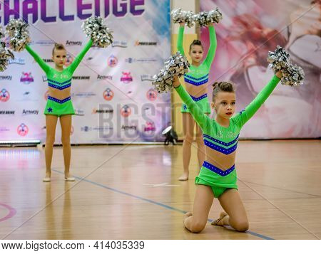 Moscow, Russia - December 22, 2019: Sports Team Young Girls In Bright Green Cheerleader Sportswear A