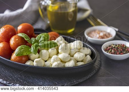 Mozzarella Cheese, Basil And Tomato Cherry In Oval Black Plate, Copy Space. Ingredients For Caprese