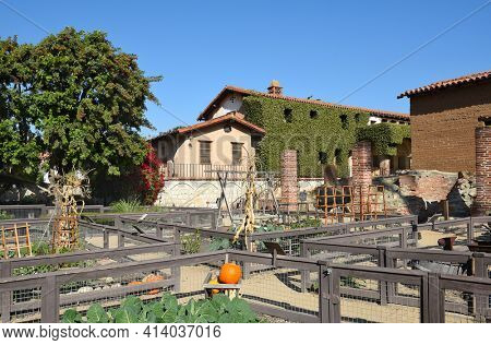 SAN JUAN CAPISTRANO, CA - DECEMBER 12, 2017: Mission San Juan Capistrano Vegetable Gardens and Wine Vat area.