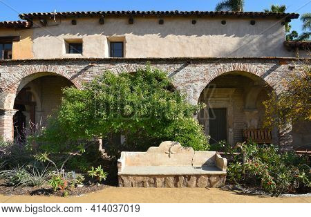 SAN JUAN CAPISTRANO, CA - DECEMBER 12, 2017: Mission San Juan Capistrano garden grounds bench in the Central Courtyard of the Mission.