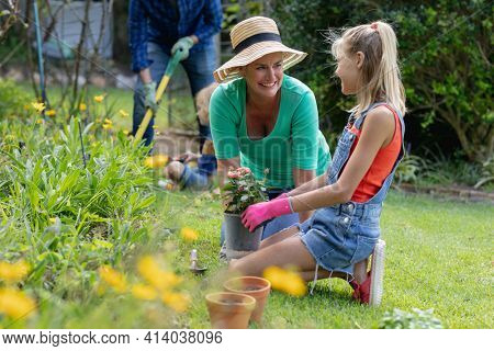 Smiling caucasian granddaughterl and grandmother talking in garden while gardening with their family. happy three generation family spending time together at home.