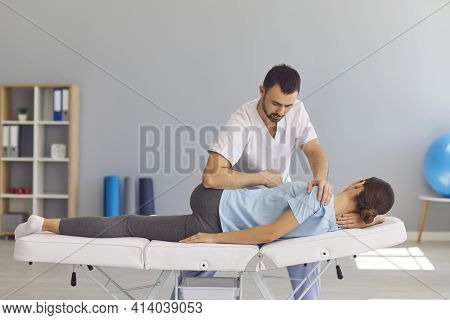Confident Man Doctor Chiropractor Or Osteopath Fixing Womans Back And Legs Joints