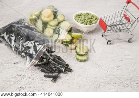 Frozen Zucchini And Beans Spilled Out Of The Bags On The Bright Table Next To A Mini Supermarket Car