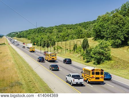 Horizontal Shot Of School Buses On A Highway.