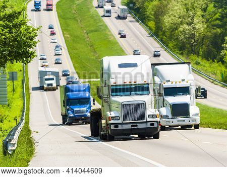 Horizontal Shot Of A Tractor Trailer Rig Leading Traffic Up A Tennessee Interstate Incline.  This Is