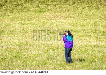 Horizontal Shot Of A Woman Photographer Standing In A Field Taking A Picture With Copy Space.