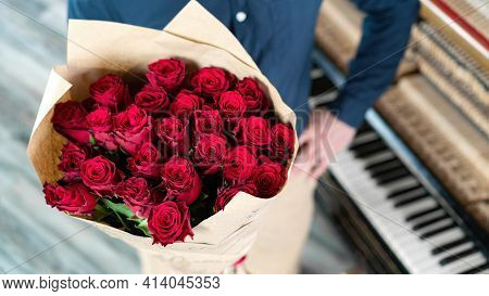 A Man In A Classic Shirt Stands Near The Piano And Holds A Luxurious Bouquet Of Red Roses As A Gift