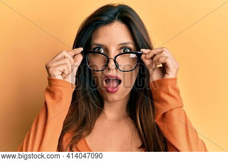 Beautiful hispanic woman wearing glasses afraid and shocked with surprise and amazed expression, fear and excited face.