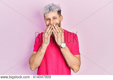 Young hispanic man with modern dyed hair wearing casual pink t shirt laughing and embarrassed giggle covering mouth with hands, gossip and scandal concept