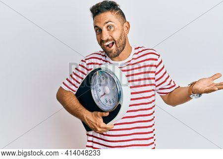 Handsome man with beard holding weight machine to balance weight loss celebrating achievement with happy smile and winner expression with raised hand