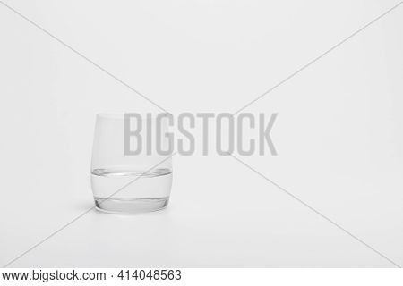 The Half Full Glass Of Pure Water Isolated On A White Background. A Drinking Glass Half Filled With