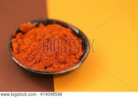 Red Pepper Powder.hot Pepper. And Condiments Concept Red Peppers In A Black Ceramic Plate On A Brown