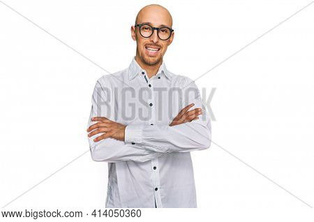Bald man with beard wearing business shirt and glasses happy face smiling with crossed arms looking at the camera. positive person.