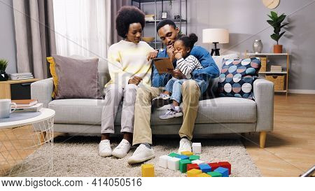 African American Cute Family Parents And Little Girl Child Sitting On Sofa In Cozy Living Room At Ho
