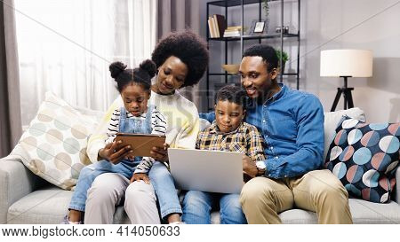 African American Young Happy Nice Family With Children Resting At Home On Couch Spending Time Togeth