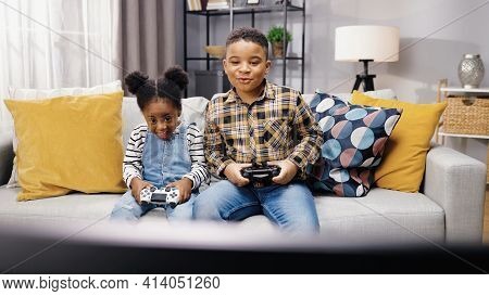 Two African American Children Sitting On Sofa In Apartment And Playing Video Games On Console In Goo