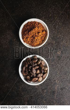 Cocoa powder and cocoa beans in bowl on black table. Top view.