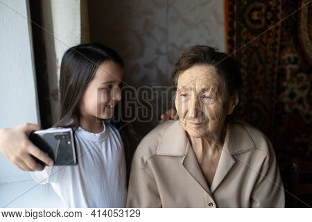 Very Old Great-grandmother And Granddaughter With A Smartphone Online