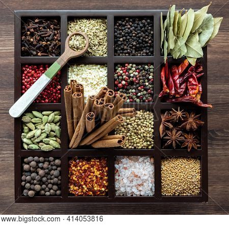 Top Down View Of A Variety Of Whole In A Compartment Box With A Wooden Spoon Of Fennel Seeds On Top.