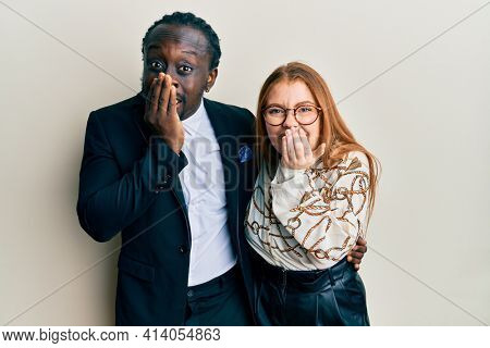 Young interracial couple wearing business and elegant clothes laughing and embarrassed giggle covering mouth with hands, gossip and scandal concept