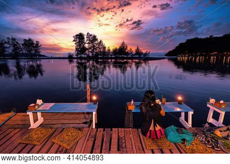 Woman drinking cocktail and watching beautiful sunset in Koh Kood island, Thailand.