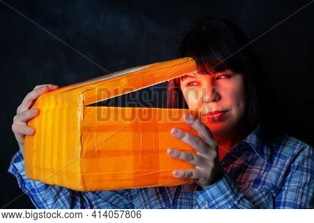 Young Caucasian Girl Opens The Package From Chinese International Delivery With A Red Light Inside A
