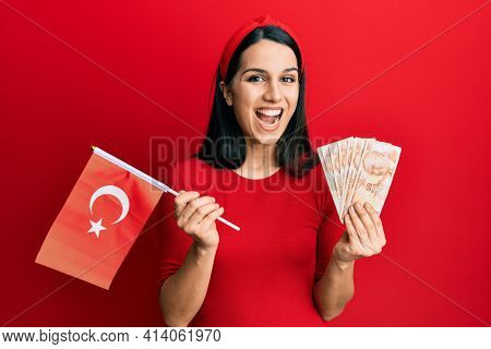 Young hispanic woman holding turkey flag and liras banknotes celebrating crazy and amazed for success with open eyes screaming excited.